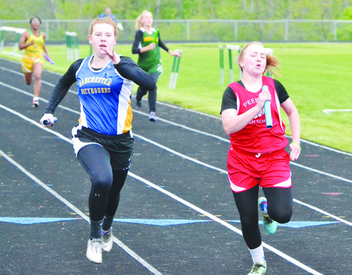 It was a race to the finish line in the Girls 4 x 100 Relay between Manchester's Katie Fetters, left, and Peebles' Breauna Shoemaker, right.  Shoemaker got the best of the battle as the anchor of the Indians' quarter, winning the race in a time of 56.37.  The Manchester foursome recorded a finish time of 56.62.  Photo by Mark Carpenter.
