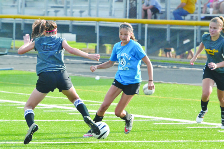Eighth grader Karissa Buttelwerth, center, forced into varsity play when other girls were out for various commitments, battles for possession with a pair of Georgetown players in July 8 action.