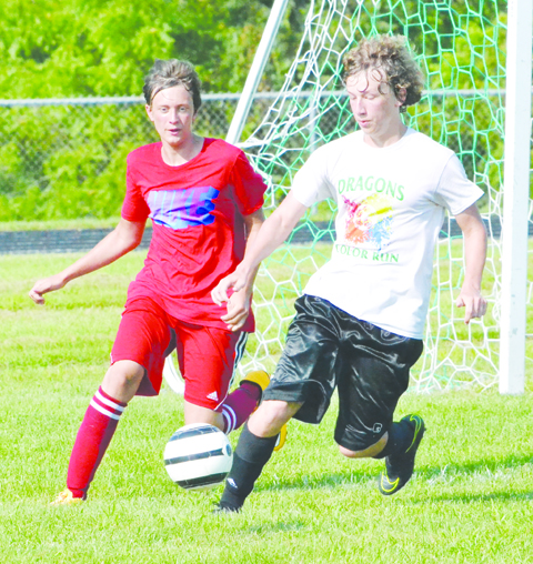 West Union's Andre Wolke, right, battles for possession during last Friday's scrimmage with Peebles.