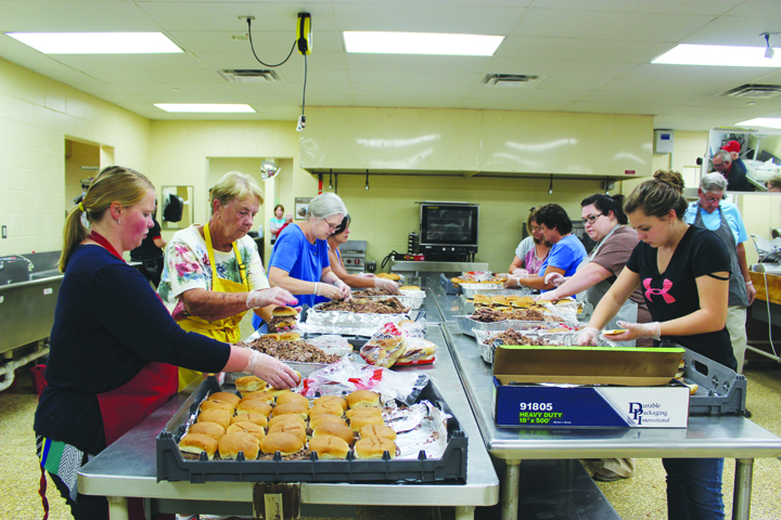 It takes a team effort, such as seen with these folks preparing the meals, to make the annual Junior Fair Beef BBQ a success year after year.