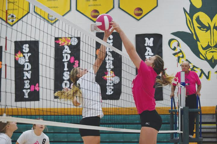North Adams' Madison Jenkins, right, goes up and over the net for this return as the Lady Devils downed Peebles in three sets last week on the annual Volley For the Cure Night.