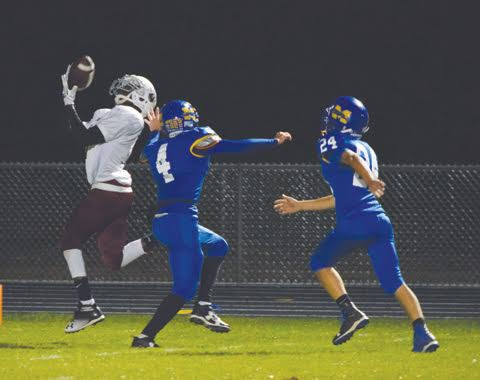 Hillcrest receiver Kevin Reid hauls in this long touchdown pass over a pair of Manchester defenders in first half action from last Friday night at Greyhound Stadium.