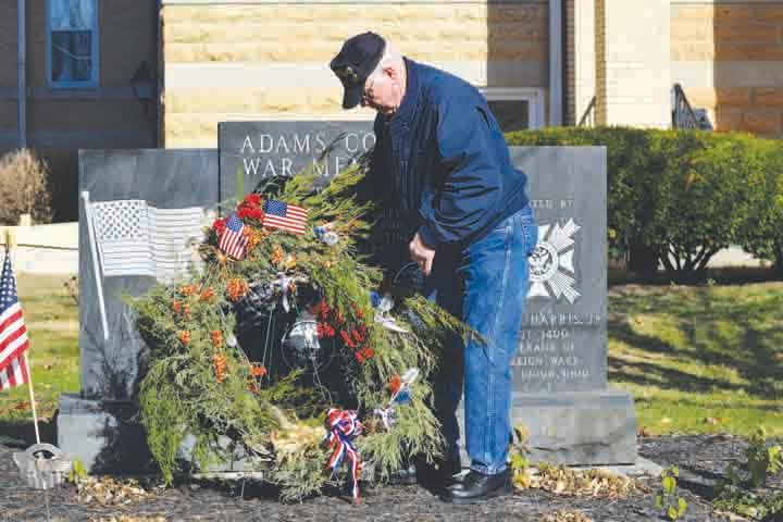 Bill Conn, President of Adams County Veterans Services, places a special wreath in front of the courthouse War Memorial commemorating the 50th anniversary of the Vietnam War and those from Adams County who lost their lives in southeast Asia.