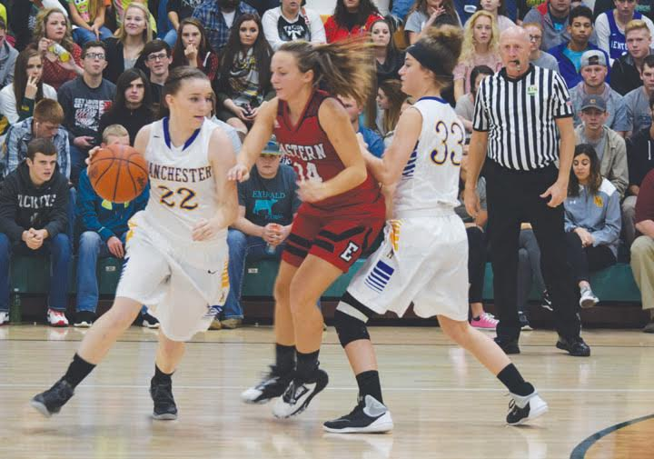 Using a screen from teammate Abby McFarland (33), Manchester guard C.J. Hobbs (22) tries to maneuver around an Eastern Brown defender during play from the annual SHAC Girls Preview on Nov. 18 at North Adams.